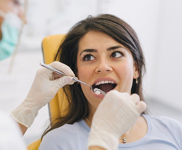 Woman having a tooth extracted