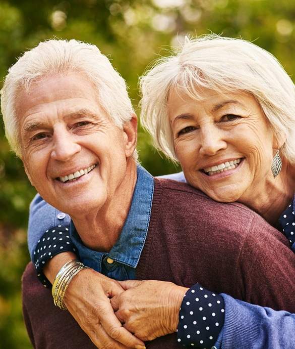 Older man and woman smiling together after dental implant tooth replacement