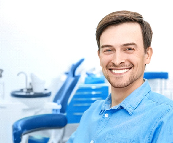 Man in blue collared shirt smiling in dental chair