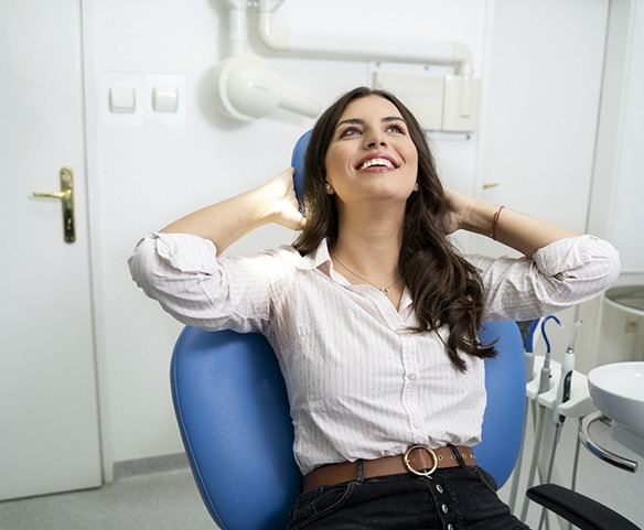 Smiling female patient casually sitting back in dental chair