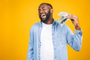 person fanning themselves with money and smiling